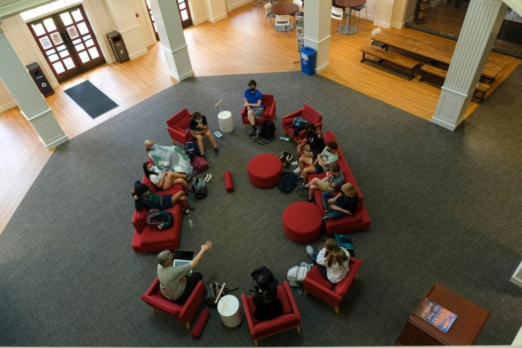 Students meet with a faculty member in the library