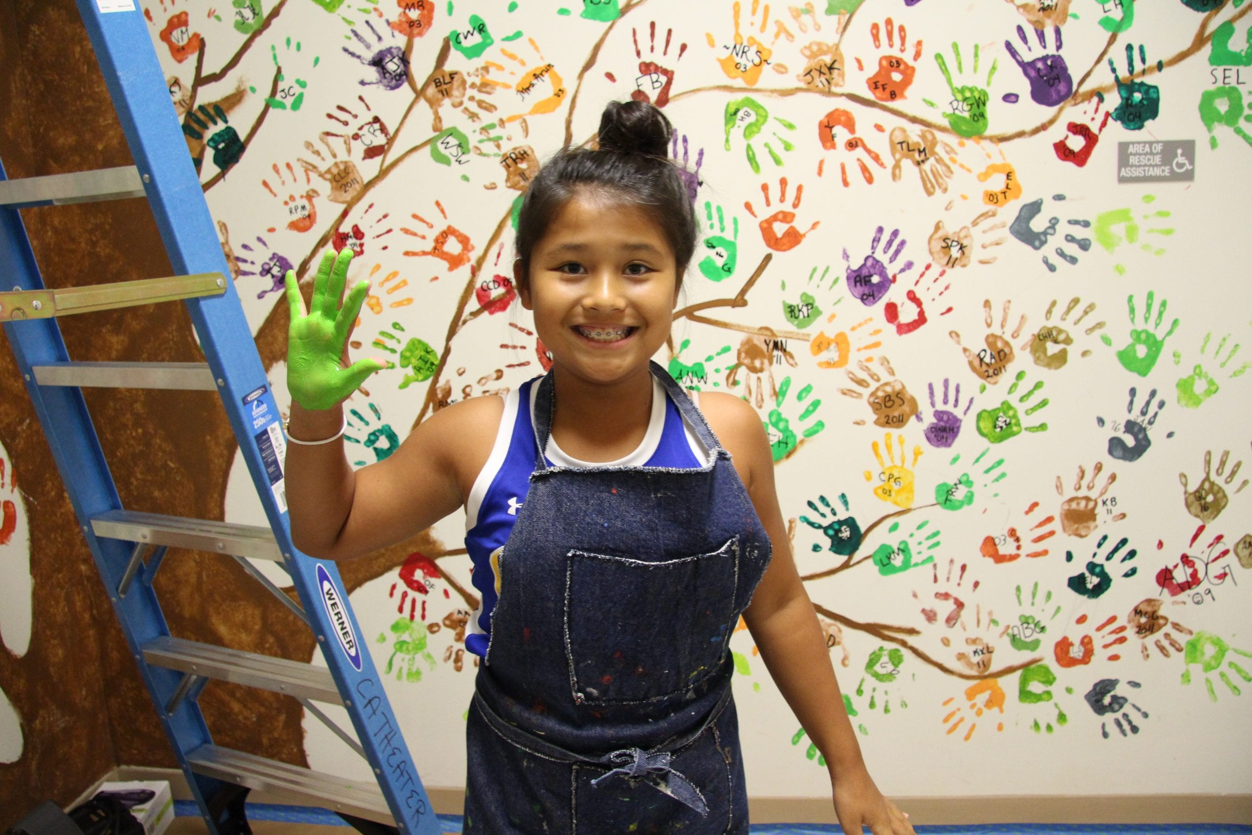 MS student in front of handprint mural